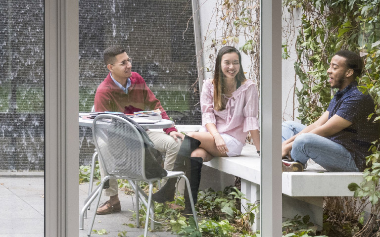 Three students sitting outside talking and laughing