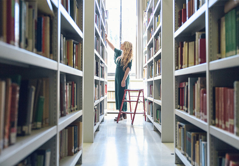 Student looking through books in library stacks