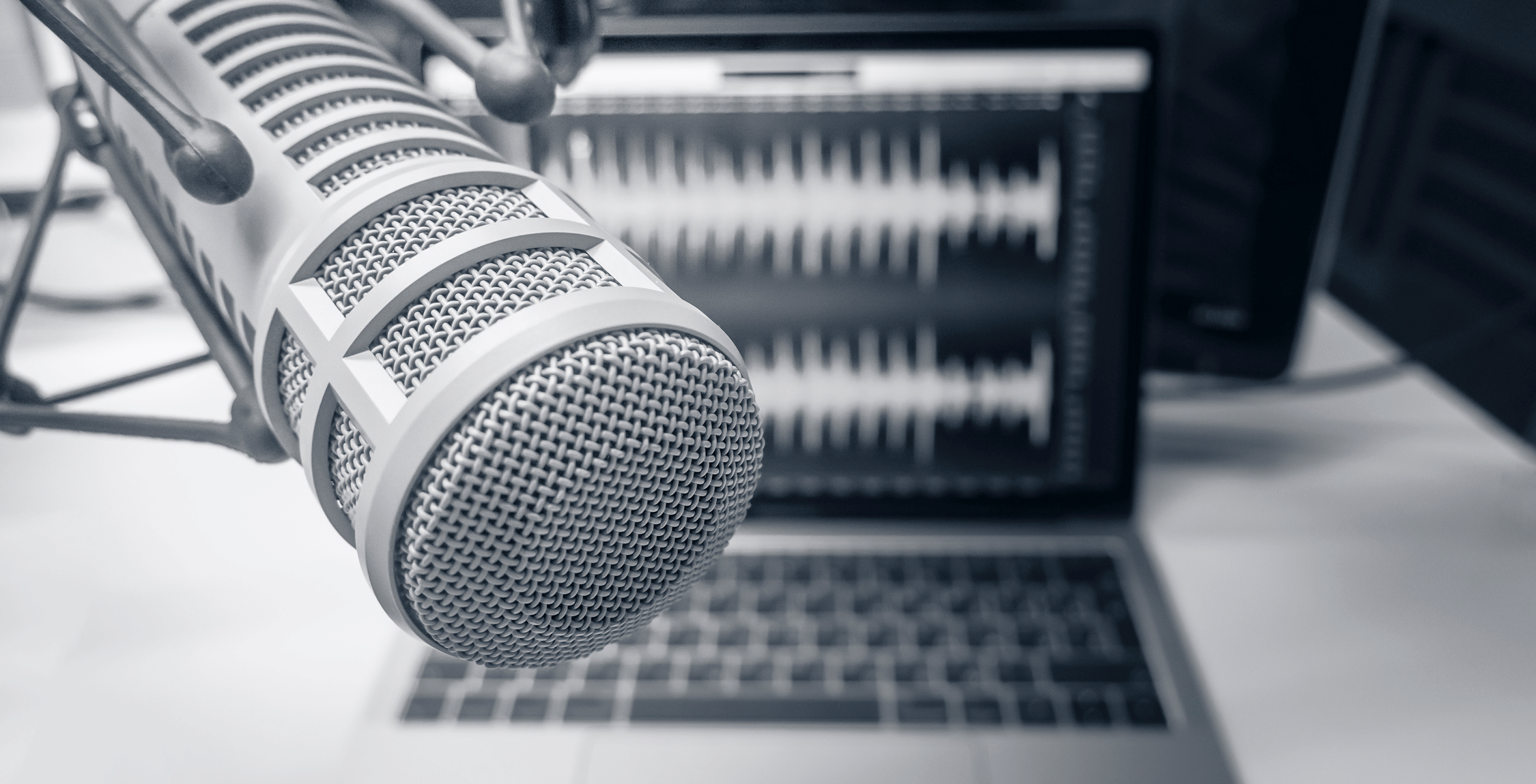 black and white photo of a recording studio microphone in front of a laptop displaying soundwaves